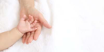 小さな赤ちゃんの手を母の手で包むイメージ